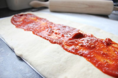 Spread pizza sauce on top of your calzone dough